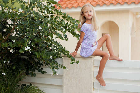 Beautiful girl sitting on the hedge in summer outdoor