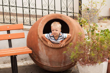 Small boy sitting in the big crock trying to get off there