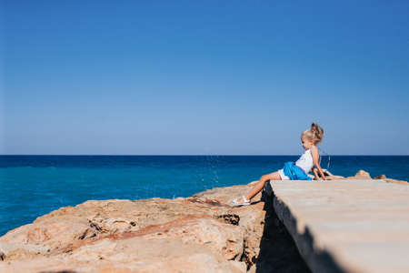 Beautiful girl posing on the rocky seashore sitting on the bridge