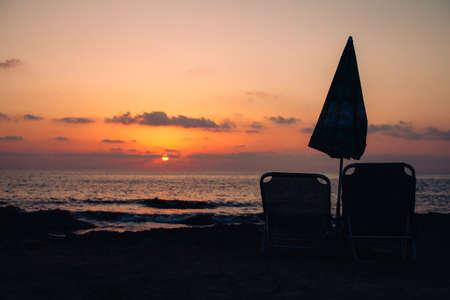 Sunset on the seashore with sunbedsand umbrella