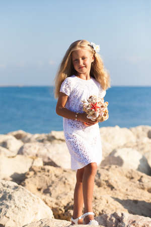 Beautiful girl with perfect hair standing on rocky seashore with the bouquet of seashells