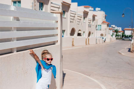 Beautiful girl in red sunglasses posing in the street under the sun