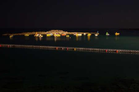 Small boats at sea shore at night uplited Stock Photo