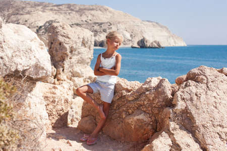 girl standing at the cliff on the seashore with her eyes shut Stock Photo