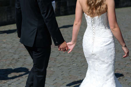 Bride and groom walking along the stony street in sunny weather shot from the back Stock Photo