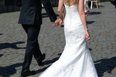 street shot: Bride and groom walking along the stony street in sunny weather shot from the back Stock Photo