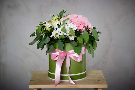 A bunch of pink and white flowers with soft linen on the box