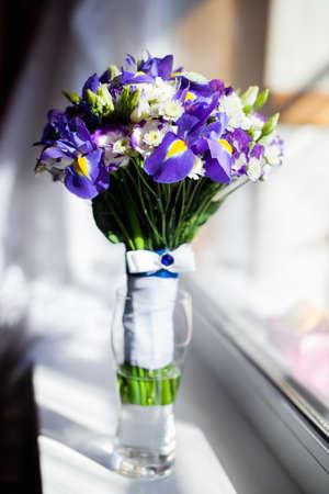 A Bucket of purple flowers standing near the window