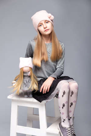 A small beautiful girl siiting on a chair with a doll in photostudio