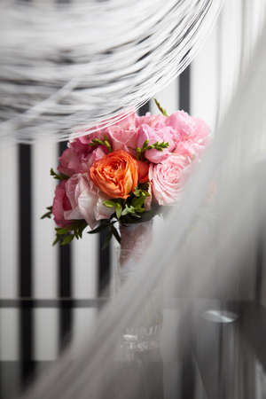 A Bucket of peony flowers standing on the glass table under the curtains near the window