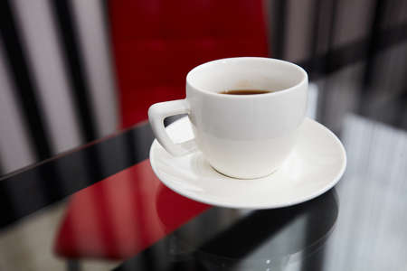 A white cup of coffee on glass table