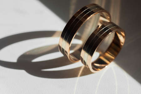 Golden wedding rings for bride and groom standing on the sides Stock Photo