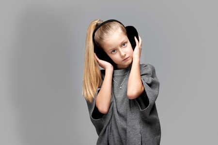 Cute stylish girl in grey dress and with winter headphones in the photostudio on grey background