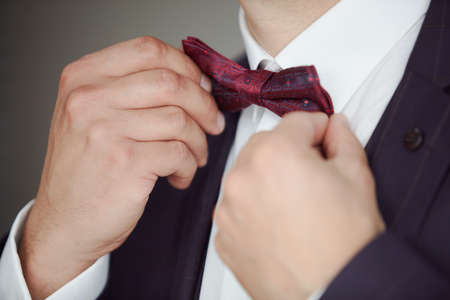 Man's hands wearing a bowtie in close-up