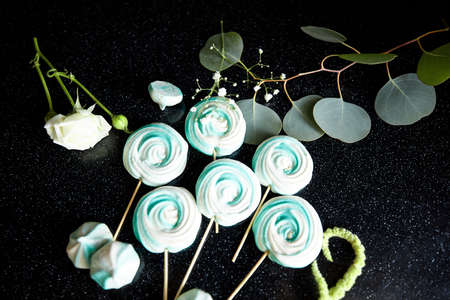 Green and white sweets on the stick on the dark background decorated with some flowers