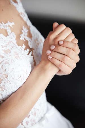 Bride's beautiful hands in fantastic white wedding dress