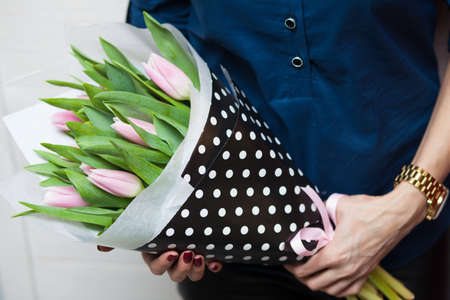A girl hoding beautiful spring tulips in her hands