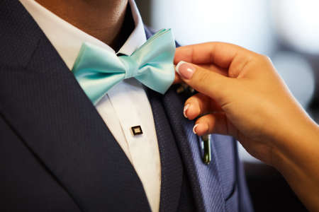 Woman's hands setting groom's bowtie in close-up