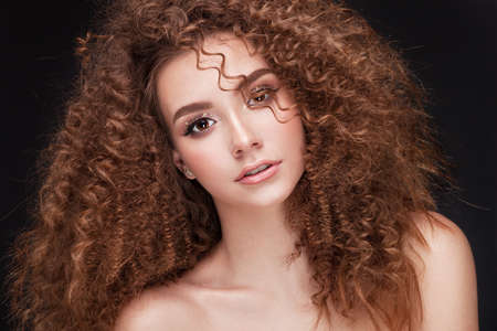 Very beautiful girl model with afro curls and soft skin in sudio on black background