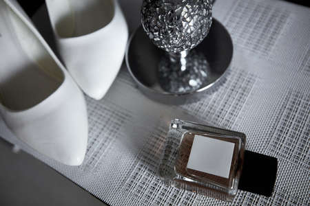 Wedding bride's elements such as shoes and perfume on the table on the striped background Stock Photo