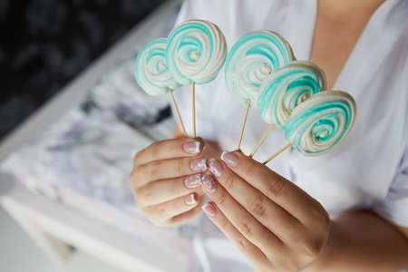 Green and white sweets on the stick in bride's hands wearing white dress Stock Photo