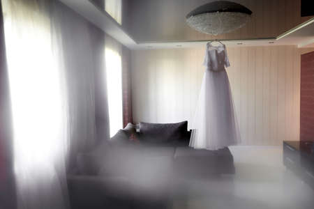 Bride's fantastic white wedding dress hanging on the lamp indoor Stock Photo