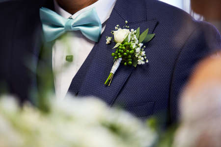 Groom's chest in suit with a boutonniere and a bowtie Stock Photo