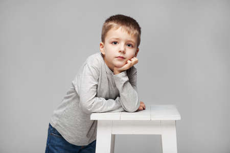 Portrait of a cute boy with standing at the chair in the photostudio on grey background