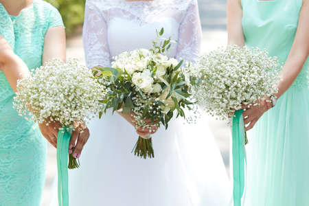 Bride and bridesmaids holding in their hands bouquets of flowers Stock Photo