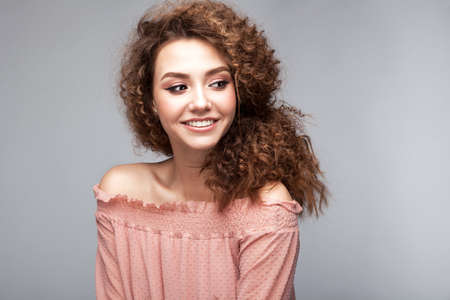 Very beautiful girl model with afro curls and soft smiling face in sudio on neutral grey background Stock Photo