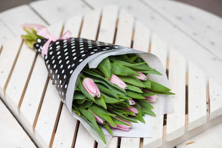 Beautiful spring pink tulips wrapped in stulish paper on a wooden background