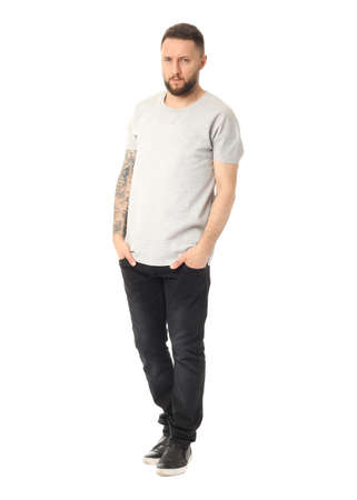 nonchalant: Handsome young man with a beard posing on white