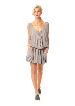 Portrait of flirtatious woman in gray tunic dress isolated