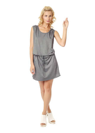 Full length of flirtatious woman with gray dress isolated