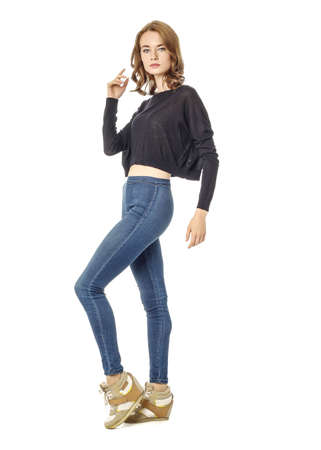 Young brunette woman standing in blue skinny jeans