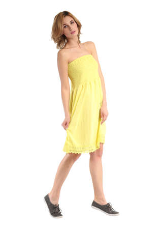 Portrait of flirtatious woman in yellow tunic dress isolated