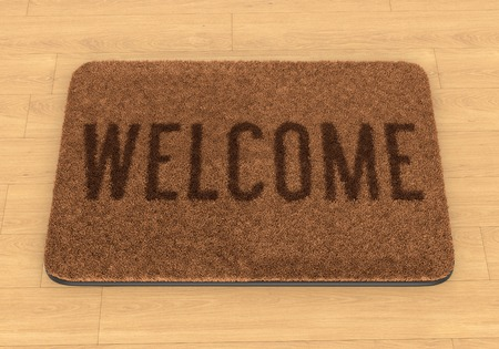 welcome door: Brown coir doormat with text Welcome on wooden floor Stock Photo