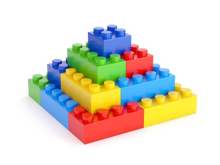 Piramide gemaakt van plastic speelgoed blokken op een witte achtergrond Stockfoto