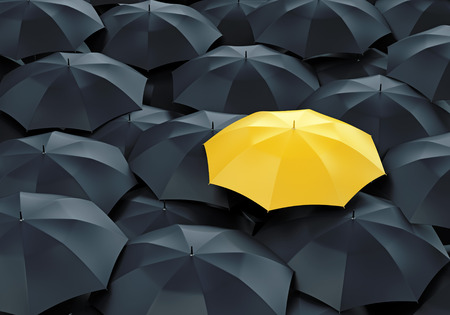 different idea: Unique yellow umbrella among many dark ones. Standing out from crowd, individuality and difference concept. Stock Photo