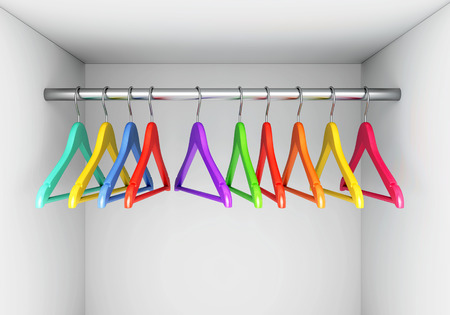 Colorful wooden cloth hangers on clothes rail in white wardrobe Stock Photo