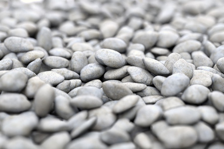 Naturally polished gray rock pebbles on sea shore. Nature beach background. 3D illustration
