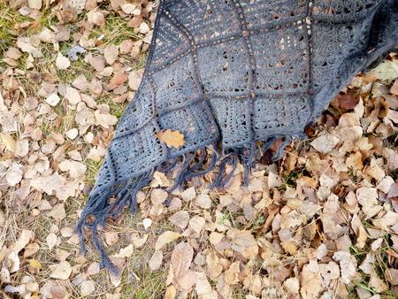Crocheted gray shawl on autumn leaves. Square motifs, fringe