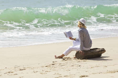 Woman with book is sitting on a stump by the wave line