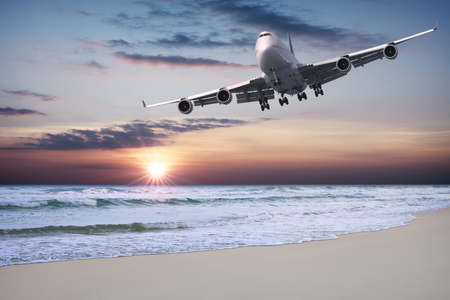 Jet liner is flying over the beach at sunset Stock Photo