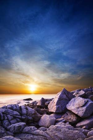 劇的な海に沈む夕日。長時間露光垂直ショット。