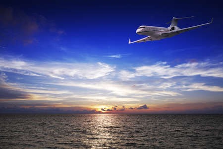 corporate jet: Luxury private jet over the sea at sunset time Stock Photo