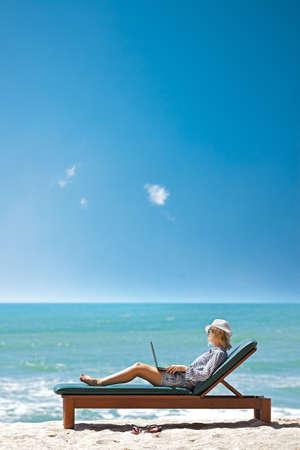 熱帯のビーチでデッキチェアでラップトップを持つ若い女性。垂直方向のショット。 写真素材