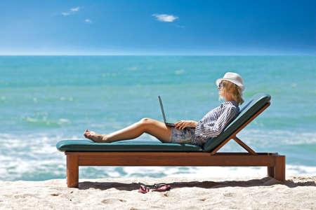 Mujer joven con el portátil en la playa tropical