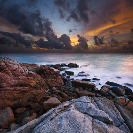 日没時の岩石の多い海岸の眺め。超広角、長時間露光ショットします。