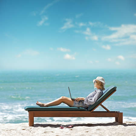 relajado: Mujer joven con ordenador portátil en la playa Foto de archivo
